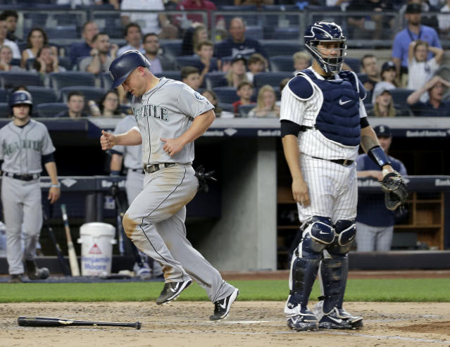 Seattle Mariners' Kyle Seager, left, scores past New York Yankees catcher Gary Sanchez on a single hit by Denard Span during the fourth inning of a baseball game at Yankee Stadium Wednesday, June 20, 2018, in New York. (AP Photo/Seth Wenig)