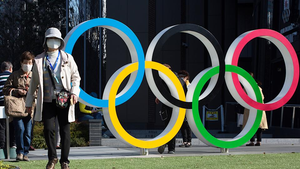 Women with surgical masks, pictured here walking next to the Olympic Rings.