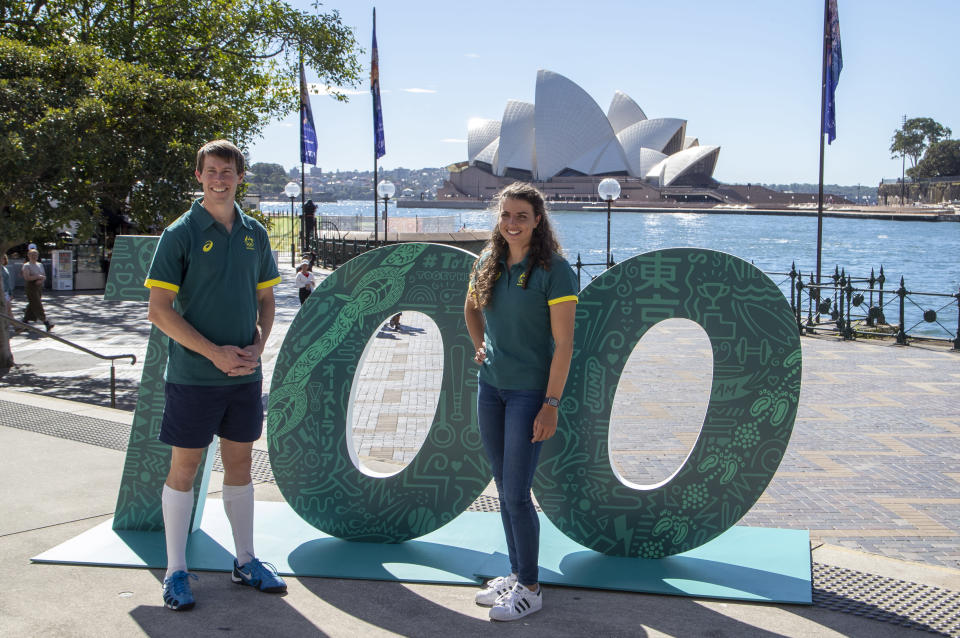 Australian Olympians Edward Fernon, modern pentathlon, and slalom canoeist Jess Fox stand by a sign at a ceremony to mark 100 days before the start of the Tokyo Olympics in Sydney Wednesday, April 14, 2021. Olympics live sites will be held across Australia during the Olympic Games, from July 23 to Aug. 8 2021, taking advantage of the one hour time zone difference for Australians to watch athletes perform. (AP Photo/Mark Baker)