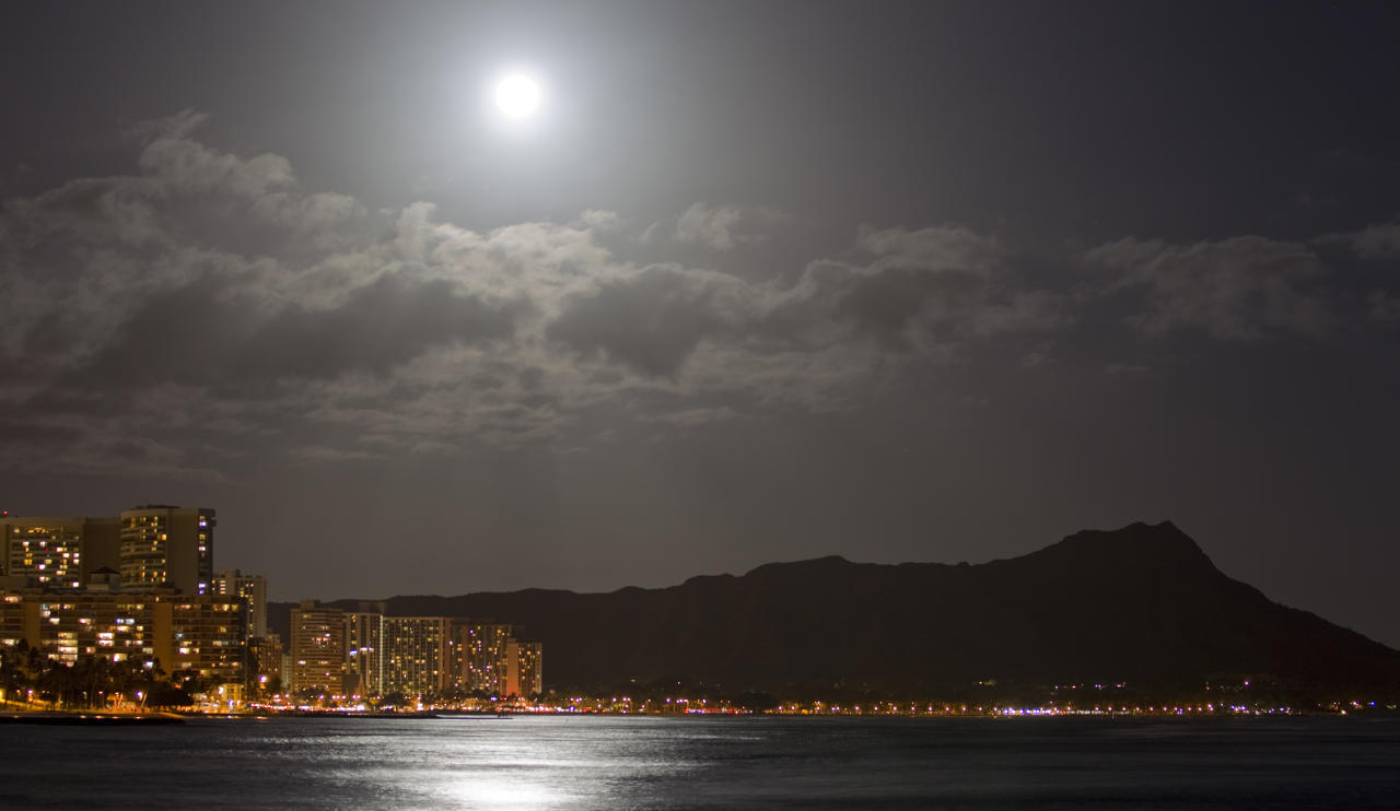 "A supermoon lights up Waikiki and Diamond Head Saturday, May 5, 2012, in Honolulu. A ""supermoon"" event happens when the moon is closest to the earth therefore the biggest and brightest full moon of the year. (AP Photo/Eugene Tanner)"