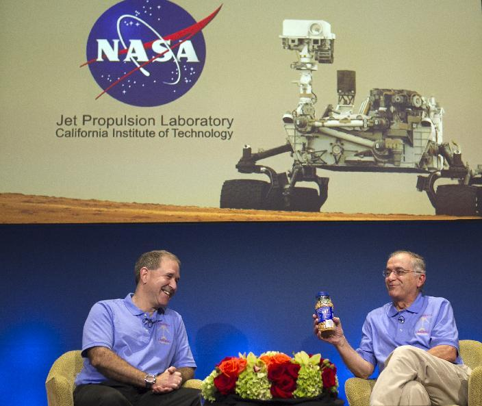"John Grunsfeld, NASA Associate Administrator, NASA Headquarters, left, and Charles Elachi, JPL Director, NASA Jet Propulsion Laboratory, present a can of ""good luck"" peanuts during an overview of the status and plans for NASA's Science Mission Directorate at NASA's JPL in Pasadena, Calif., Sunday, August 5, 2012. After traveling 8 1/2 months and 352 million miles, Curiosity will attempt a landing on Mars Sunday night. (AP Photo/Damian Dovarganes)"