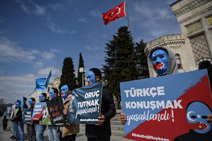 """Demonstrators wearing a mask painted with the colors of the flag of East Turkestan hold placards reading """"Speaking Turkish , banned"""" and """"fasting in Ramadan, banned"""" during a protest by supporters of the Uyghur minority on Thursday at Beyazid Square in Istanbul, Turkey. At least one million Uyghurs and people from other mostly Muslim groups have been held in camps in northwestern Xinjiang, China, according to rights groups, who accuse Chinese authorities of forcibly sterilizing women and imposing forced labor."""