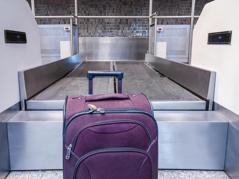 Suitcase in front of an airport mat waiting to be dispatched