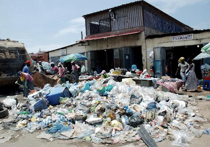 Angolans walk past a pile of uncollected garbage in Luanda, on January 20, 2016 (AFP Photo/)