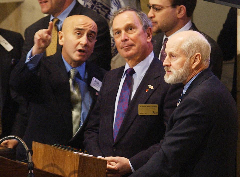 NEW YORK, UNITED STATES:  New York City Mayor Michael Bloomberg (C), and former New York Stock Exchange President William Johnston (R) listens to New York Stock Exchange Chairman Richard Grasso (R) on the bell podium before Bloomberg rang the opening bell to begin trading 02 January, 2002.    AFP PHOTO  Henny Ray ABRAMS (Photo credit should read HENNY RAY ABRAMS/AFP via Getty Images)