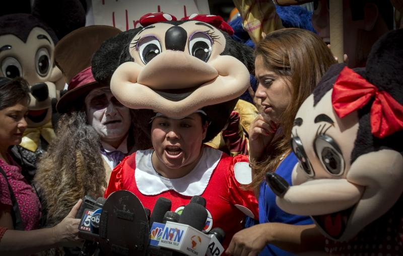 A woman dressed as Minnie Mouse speaks during a rally in support of organizing costumed characters in New York's Times Square