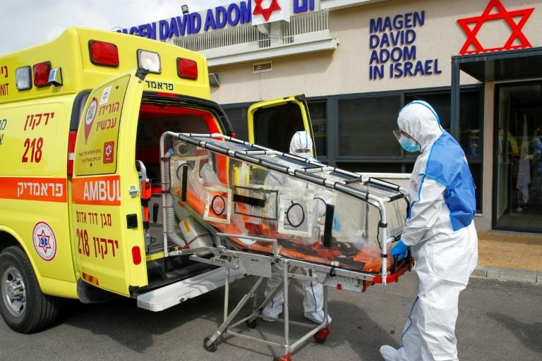 Israeli paramedics at a coronavirus national operations centre unload a containment chamber during a response training exercise in the central Israeli city of Kiryat Ono