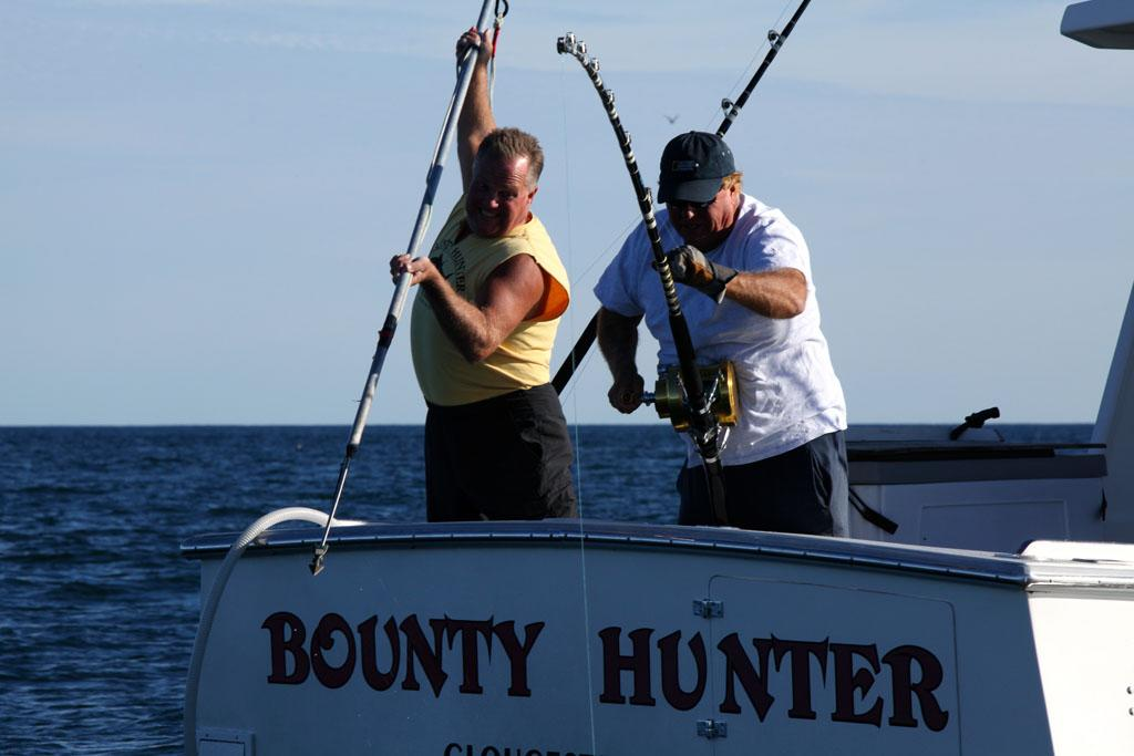 Gloucester, MA - Bounty Hunter Captain Bill Monte reeling in a fish while his First Mate Scott Ferriero is ready with the harpoon.