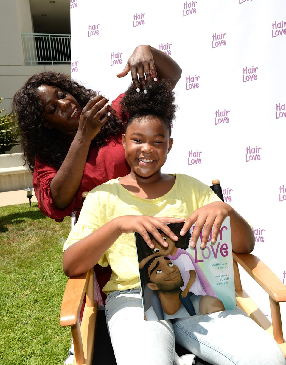 """A young Black girl gets her natural hair styled at a """"Angry Birds Movie 2"""" and """"Hair Love"""" spa takeover in Culver City, Calif. (Photo by Andrew Toth/Getty Images for Columbia Pictures)"""