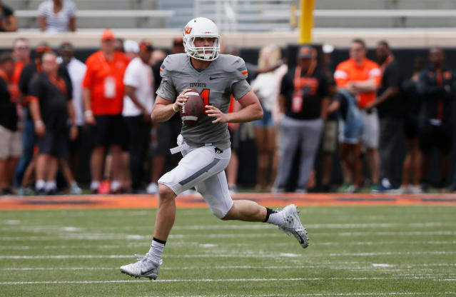 FILE - In this April 15, 2017, file photo, Oklahoma State quarterback Taylor Cornelius (14) carries during an intra squad spring NCAA college football game in Stillwater, Okla. For the first time in more than three years, Oklahoma State coach Mike Gundy will have a new starting quarterback. Mason Rudolph started 41 games for the Cowboys and left with many of the most significant school records. Taylor Cornelius appears ready to step in. The 6-foot-6, 232-pound senior has taken control of the position during the spring. (AP Photo/Sue Ogrocki, File)
