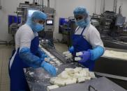 Workers sort halloumi cheese at the Petrou Bros Dairy in Aradippou