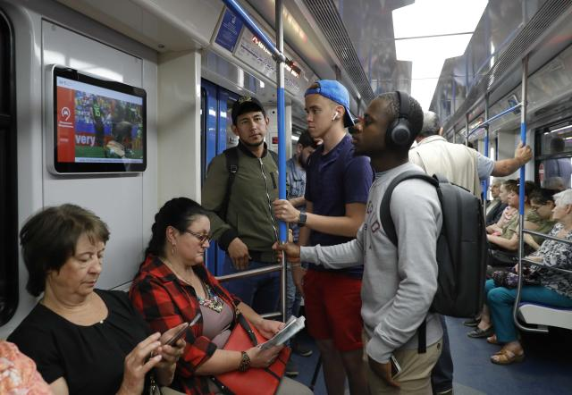Commuters watch a live broadcast of the 2018 World Cup match between Denmark and Australia on an electronic screen in a metro coach in Moscow, Russia June 21, 2018. REUTERS/Tatyana Makeyeva