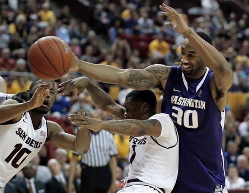Washington's Desmond Simmons (30) battles Arizona State's Evan Gordan (10) and Jahii Carson (1) during the first half of an NCAA college basketball game, Saturday, Feb. 23, 2013, in Tempe, Ariz. (AP Photo/Matt York)