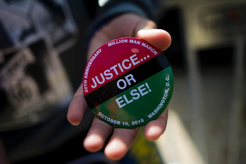 A man displays a button supporting the Justice or Else! rally on the National Mall in Washington, DC on October 10, 2015 (AFP Photo/Andrew Caballero-Reynolds)