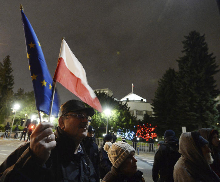 A man holding a Poland and European Union flags take part in a protest outside Poland's parliament building as lawmakers voted to approve the much-criticized legislation that allows politicians to fire judges who criticize their decisions, in Warsaw, Poland, Thursday, Jan. 23, 2020. Poland's lawmakers gave their final approval Thursday to legislation that will allow politicians to fire judges who criticize their decisions, a change that European legal experts warn will undermine judicial independence. (AP Photo/Czarek Sokolowski)