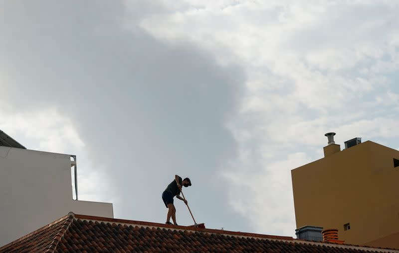 A person cleans the ash from a roof as smoke rises in the background following the eruption of a volcano on the Canary Island of La Palma