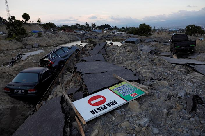 """<p>Cars are trapped in sinking ground after an earthquake hit at Balaroa sub-district in Palu, Sulawesi Island, Indonesia on Oct.1, 2018. The sign reads """"We have a party"""". (Photo: Beawiharta/Reuters) </p>"""