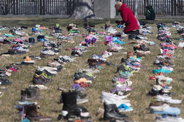 <p>A woman looks at some of the approximately seven thousand shoes representing lost children to guns since the Dec. 14, 2012 shooting at Sandy Hook Elementary School in Newtown, Conn., on the East Front of the U.S. Capitol in Washington, March 13, 2018. (Photo: Michael Reynolds/EPA-EFE/REX/Shutterstock) </p>