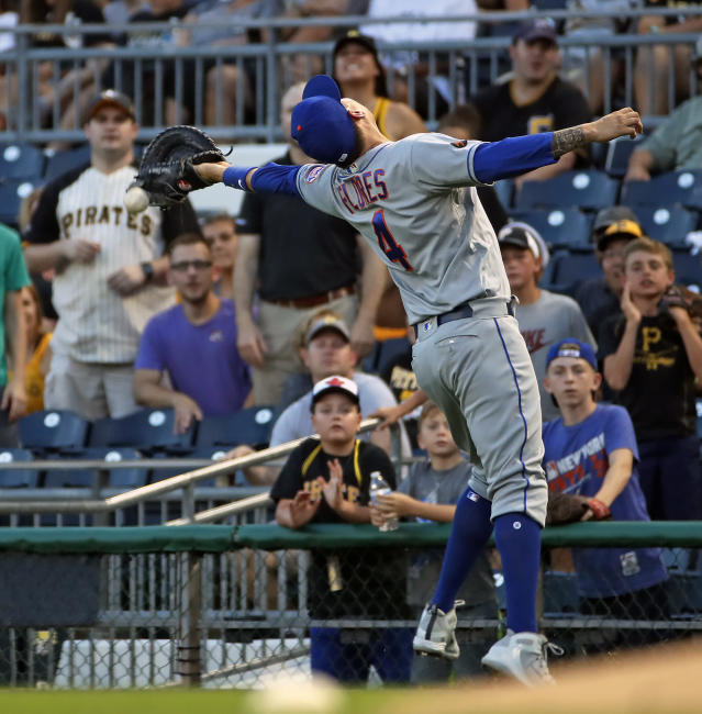 New York Mets first baseman Wilmer Flores can't handle a foul ball along the first base line hit by Pittsburgh Pirates' Josh Bell during the fourth inning of a baseball game in Pittsburgh, Thursday, July 26, 2018. (AP Photo/Gene J. Puskar)