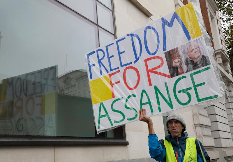 A man stands outside court with a sign saying 'freedom for Assange' (AP)