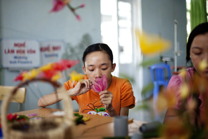In this photo taken Aug. 7, 2012, Ho Thi Lang, 18, left, and Pham Thi Thuy Linh, 21, learn how to make artificial flowers at the supporting center for victims of Agent Orange in Danang, Vietnam. The children were born with physical and mental disabilities that the center's director said were caused by their parents' exposure to the chemical dioxin in the defoliant Agent Orange. Washington was slow to respond, but on Thursday, Aug. 9, 2012 the U.S. for the first time will begin cleaning up leftover dioxin that was stored at the former military base, now part of Danang's airport. (AP Photo/Maika Elan)