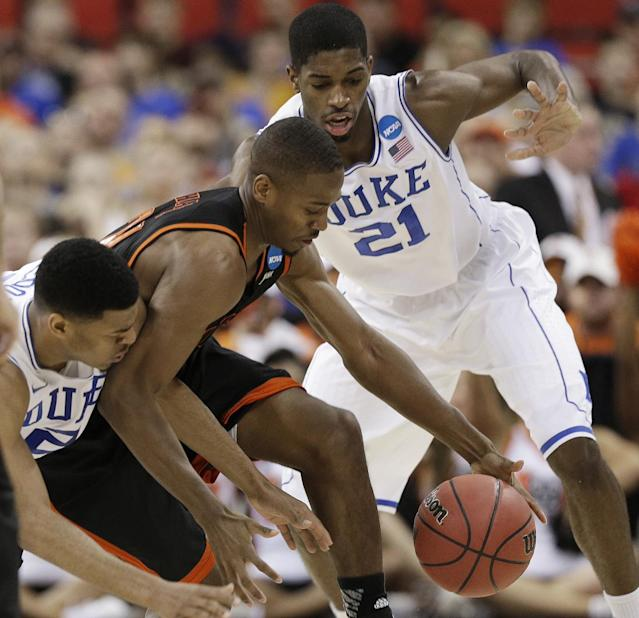 Mercer guard Langston Hall (21) moves the ball under pressure from Duke guard Quinn Cook, left, and Duke Amile Jefferson (21) during the second half of an NCAA college basketball second-round game, Friday, March 21, 2014, in Raleigh, N.C