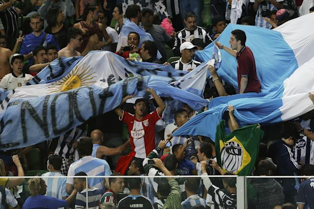 Fans hold a large Argentine flag and sing during a training session of the Argentine national soccer team at Independencia Stadium in Belo Horizonte, Brazil, Wednesday, June 11, 2014. Argentina will play in group F of the Brazil 2014 soccer World Cup. (AP Photo/Bruno Magalhaes)