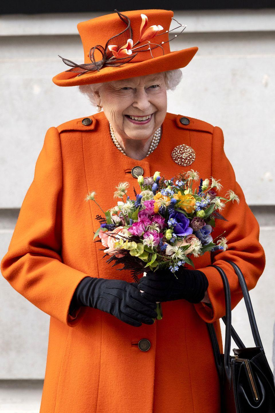 <p>Here she is in a bright orange coat and hat with tonal floral accents. She accessorized her look with earrings, a multi-strand pearl necklace, black gloves, a tonal purse, and a colorful bouquet. </p>