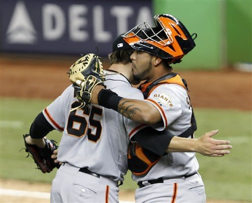 San Francisco Giants relief pitcher Steve Edlefsen (65) and catcher Hector Sanchez congratulate each other after defeating the Miami Marlins 14-7 during a baseball game on Thursday, May 24, 2012, in Miami. (AP Photo/Wilfredo Lee)