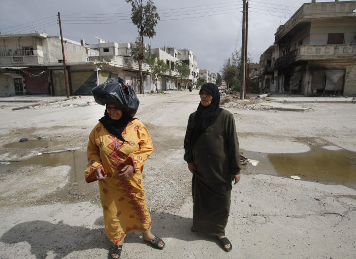 In this picture taken during a UN observer-organized tour, Syrian women walk in an empty street in front of destroyed shops during the UN observers' visit to Homs city, central Syria, on Thursday, May 3, 2012. Syrian security forces stormed dorms at a northwestern university to break up anti-government protests there, killing at least four students and wounding several others with tear gas and live ammunition, activists and opposition groups said Thursday. (AP Photo/Muzaffar Salman)