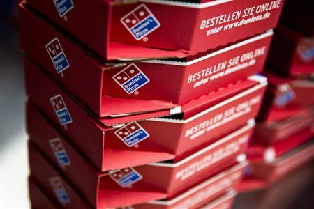 Delivery boxes for take-away pizzas are stacked at a Domino's Pizza store in Berlin