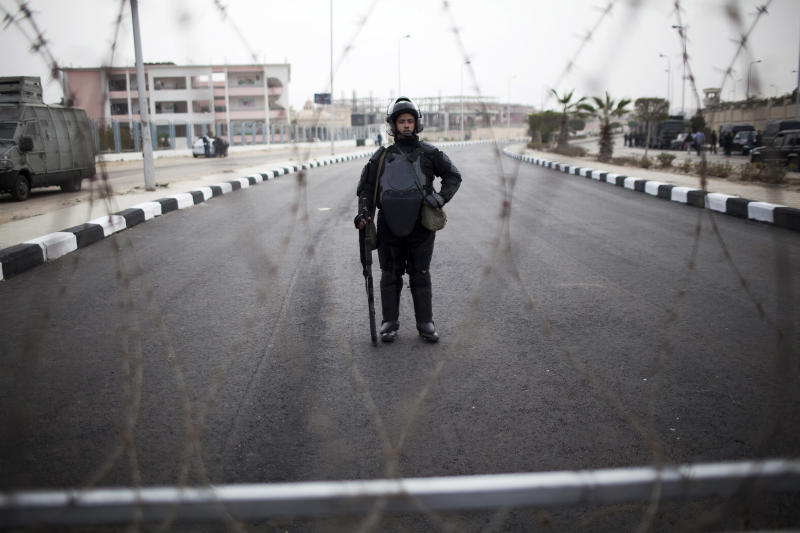 A riot policeman stands guard behind barbed wire outside of a police academy compound were the trial of ousted President Mohammed Morsi will be held in Cairo, Egypt, Monday, Nov. 4, 2013. The deposed Islamist president is to go on trial Monday on charges of incitement of violence and murder, in what will be Morsi's first public appearance since his ouster in a coup on July 3. (AP Photo/Manu Brabo)