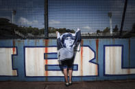 A fan wrapped in a flag with an image of Diego Maradona leans on the fence of the Gimnasia y Esgrima stadium in La Plata, Argentina, Wednesday, Nov. 25, 2020. The Deigo Maradona, the Argentine soccer great who was among the best players ever and who led his country to the 1986 World Cup title before later struggling with cocaine use and obesity, died from a heart attack on Wednesday at his home in Buenos Aires. He was 60. (AP Photo/Maria Paula Avila)