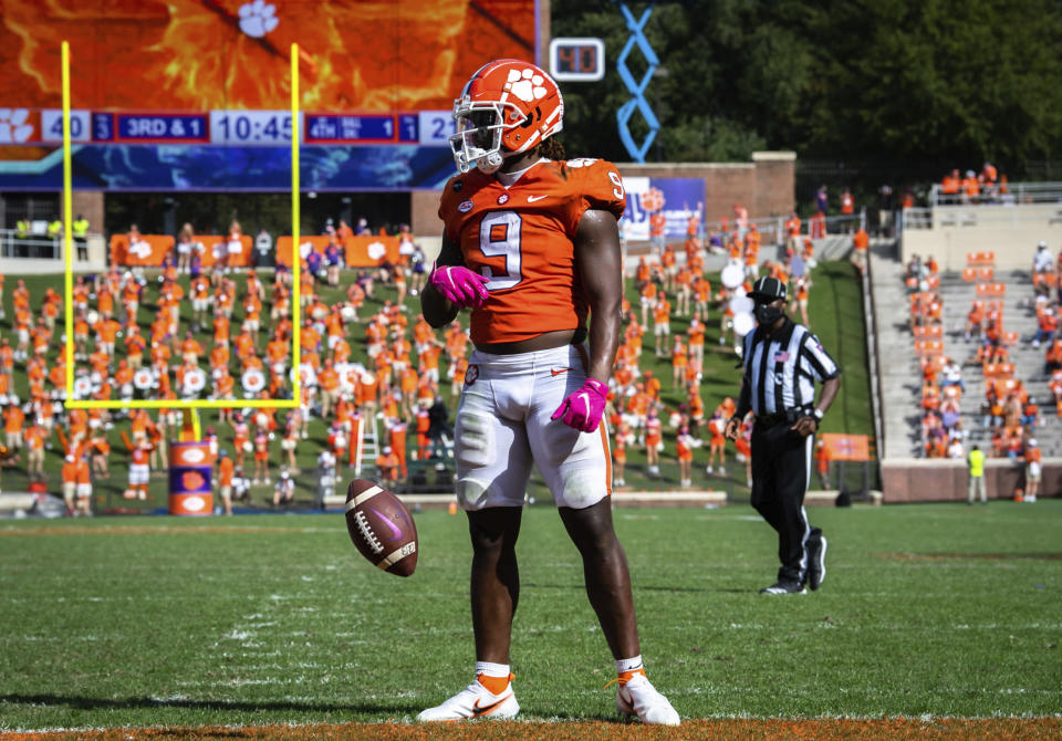 FILE - In this Oct. 24, 2020, file photo, Clemson running back Travis Etienne (9) spins the ball out of his hands after scoring a touchdown during an NCAA college football game against Syracuse in Clemson, S.C. The defense for No. 4 Notre Dame has been solid all season during a 6-0 start. It is about to face its biggest challenge. The Fighting Irish will host top-ranked Clemson on Saturday. The Tigers will be without star quarterback Trevor Lawrence. The Tigers have top running back Travis Etienne. (Ken Ruinard/Pool Photo via AP, File)