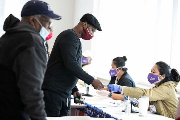 PHOTO: Voters check-in with poll workers to cast their ballots at the Metropolitan Library on Nov. 3, 2020, in Atlanta. (Jessica Mcgowan/Getty Images)