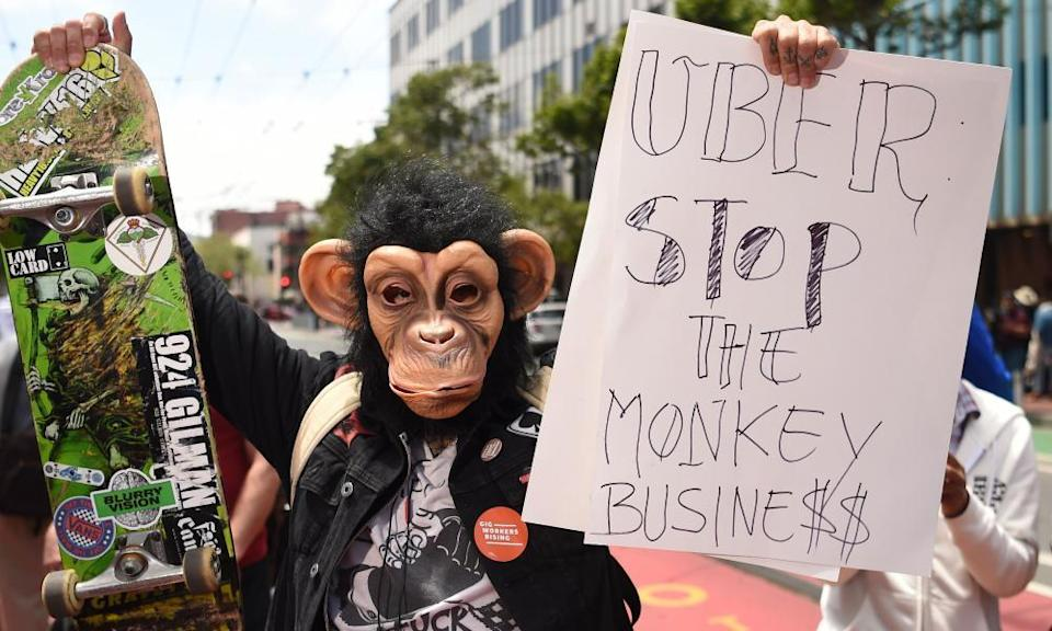 A man in a monkey mask holds up a sign as people block an intersection while protesting Uber and Lyft near Uber's headquarters office in San Francisco, California, on 8 May 2019.
