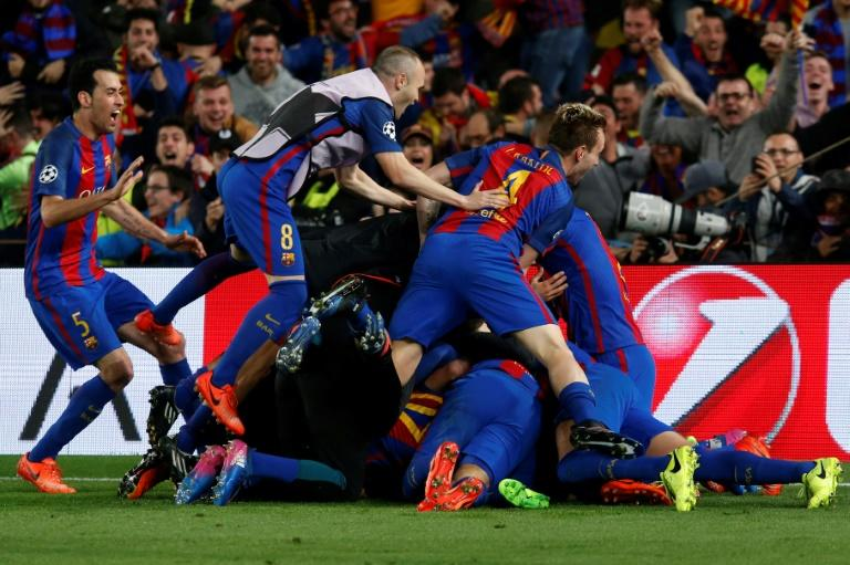 Barcelona players pile onto Sergi Roberto after his winning goal in the Champions League match against Paris Saint-Germain at the Nou Camp stadium on March 8, 2017
