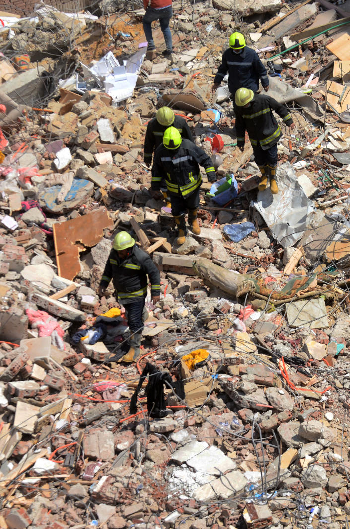 Rescuers look for victims on the rubble of a collapsed apartment building in the el-Salam neighborhood, in Cairo, Egypt, Saturday, March 27, 2021. A nine-story apartment building collapsed in the Egyptian capital early Saturday, killing at several and injuring about two dozen others, an official said. (AP Photo/Tarek wajeh)