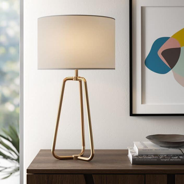 """With almost 2,000 reviews and a 4.8-star rating, you won't find a more top-rated lamp on this list. It comes in a brushed nickel and blackened bronze color, too. This LED-compatible lamp has a on/off switch near the socket and almost off-white linen shade. If you're into more of an <a href=""""https://www.huffpost.com/entry/stores-to-buy-industrial-furniture-and-decor-online_l_5f5a319ac5b62874bc1957a0"""" data-ylk=""""slk:industrial look"""" class=""""link rapid-noclick-resp"""">industrial look</a>, this lamp is probably your best bet. It does require a 60-watt bulb. <a href=""""https://fave.co/2H3xxbU"""" rel=""""nofollow noopener"""" target=""""_blank"""" data-ylk=""""slk:Find it for $63 at AllModern"""" class=""""link rapid-noclick-resp"""">Find it for $63 at AllModern</a>."""