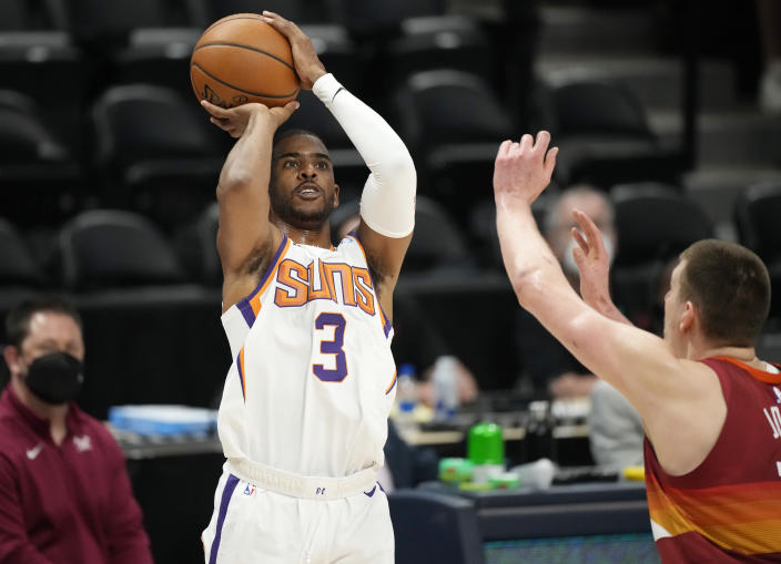 Phoenix Suns guard Chris Paul, left, shoots for a basket as Denver Nuggets center Nikola Jokic defends in the first half of Game 4 of an NBA second-round playoff series Sunday, June 13, 2021, in Denver. (AP Photo/David Zalubowski)