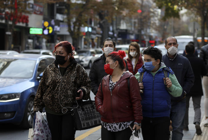People wearing masks to help protect against the spread of coronavirus, walk, in Ankara, Turkey, Monday, Nov. 30, 2020. Turkey's President Recep Tayyip Erdogan has announced Monday the most widespread lockdown so far amid a surge in COVID-19 infections, extending curfews to weeknights and full lockdowns over weekends.(AP Photo/Burhan Ozbilici)