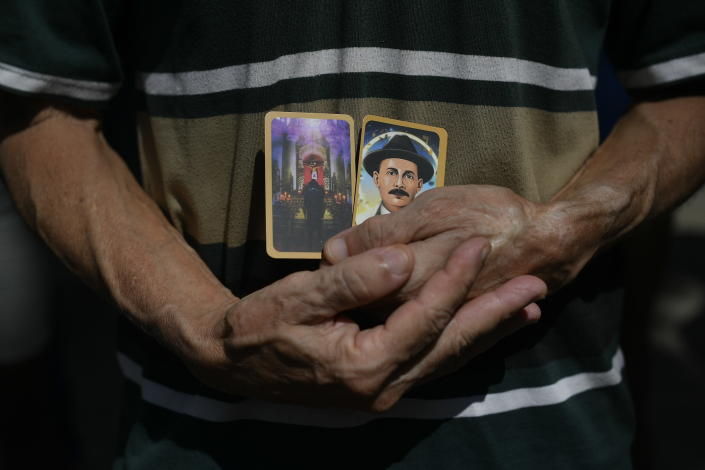 """A man holds images of the late, Venezuelan Dr. Jose Gregorio Hernandez on the day of his Beatification ceremony outside the church that guards his remains in La Candelaria neighborhood of Caracas, Venezuela, Friday, April 30, 2021. Known as the """"doctor of the poor, Hernandez will be beatified Friday by the Catholic church, a step towards sainthood. (AP Photo/Matias Delacroix)"""