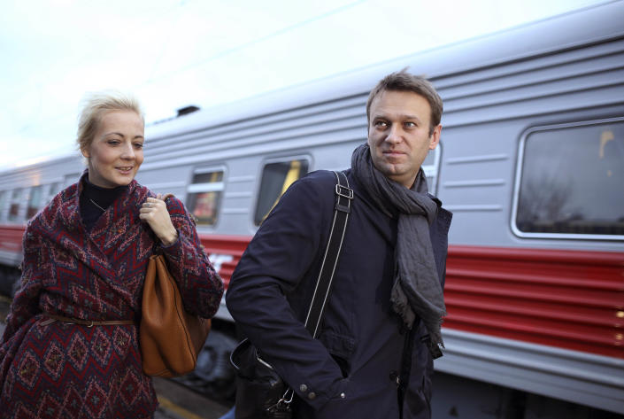 Russian opposition leader Alexei Navalny, right, with his wife Yulia, as he arrives in Kirov, Russia, to attend a trial in Kirov, Russia, Wednesday, Oct. 16, 2013. A Russian courthouse in Kirov set Navalny free in July, the day after he was convicted of embezzlement and sentenced to five years in prison. Navalny has appealed both the conviction and the sentence. (AP Photo/Evgeny Feldman)