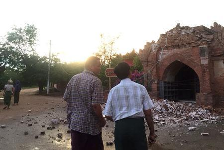 Two men look at a collapsed entrance of a pagoda after an earthquake in Bagan, Myanmar August 24, 2016. REUTERS/Stringer
