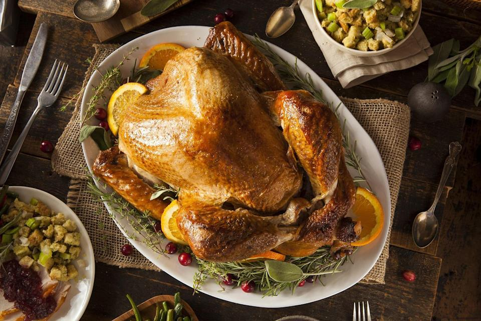 """<p>To keep your turkey nice and hot while the rest of your Thanksgiving meal cooks, simply remove the turkey from the roaster, cover it with foil and insulate it with some clean towels. Don't <a href=""""https://www.thedailymeal.com/cook/turkey-roasting-carving-tips?referrer=yahoo&category=beauty_food&include_utm=1&utm_medium=referral&utm_source=yahoo&utm_campaign=feed"""" rel=""""nofollow noopener"""" target=""""_blank"""" data-ylk=""""slk:carve the turkey"""" class=""""link rapid-noclick-resp"""">carve the turkey</a> until right before serving it. A turkey needs to rest before you carve it so the juices don't run over; removing it from the oven before dinner is actually an essential step.</p>"""