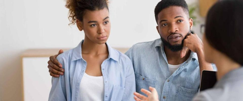 Young serious afro couple listening to their investment advisor during financial consultation in the office.  Selective focus