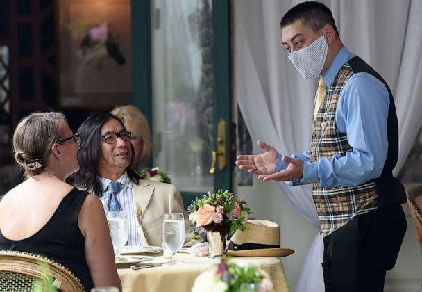 PHOTO: A waiter from The Inn at Little Washington, one of the countrys most renowned restaurants, wears a face mask while talking to customers on the first day of Virginia's phase one reopening in Washington, Va., on May 29, 2020. (Olivier Douliery/AFP via Getty Images)