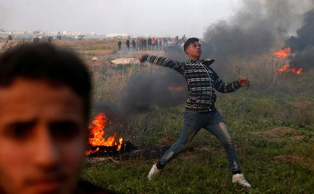 A Palestinian demonstrator hurls stones towards Israeli troops during clashes, near the border with Israel in the east of Gaza City January 12, 2018.  REUTERS/Mohammed Salem