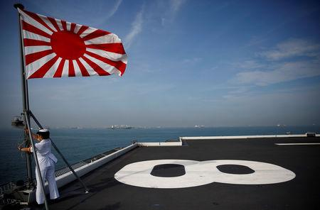 A sailor raises the Japanese naval ensign on the deck of Japanese helicopter carrier Kaga before its departure for naval drills in the Indian Ocean, Indonesia September 22, 2018. Picture taken on September 22, 2018. REUTERS/Kim Kyung-Hoon