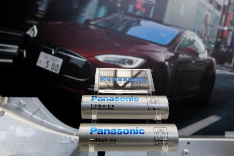 Panasonic Corp's lithium-ion batteries, which are part of Tesla Motor Inc's Model S and Model X battery packs, are displayed in front of a poster of a Tesla Model S during a news conference at the Panasonic Center in Tokyo, Japan, November 19, 2013. REUTERS/Yuya Shino/Files